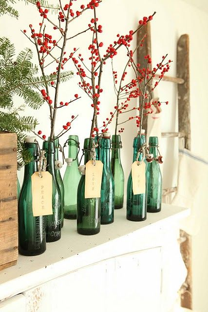 Festive green colored bottles holding branches of red berries can make a windowsil look very Christmassy