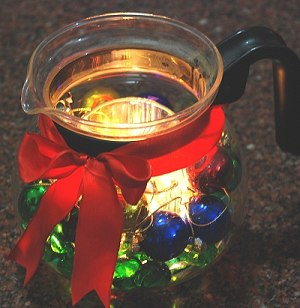 A Glass Tea Kettle is transformed into a glowing centerpiece for a Christmas table.